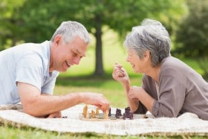 Side view of a happy senior couple playing chess at the park